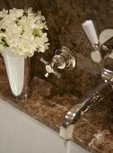 A detail of a traditional bathroom, showing a fitted bath with marble surround, chrome taps, water running, flowers in silver vase