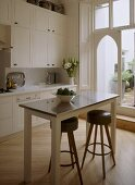 A detail of a modern, country kitchen with dining area, painted units, table, pair of stools, wood floor, door out to garden