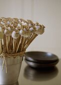 A detail of an arrangement of dried poppy seed heads in steel pot