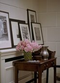 A detail of a modern hallway with a dark wood side table with drawers, a collection of framed photographs on shelf, tiled wall