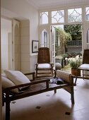 A modern country sitting room with French doors opening out on to garden, bamboo cane day bed, chairs, tiled floor