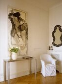Artwork above metal side table next to white covered armchair