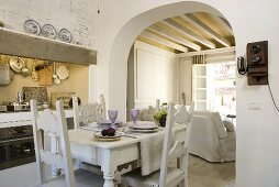 Open plan design dining room (country home style) with carved chairs and a view through the rounded doorway to the timber beam ceiling in the living room