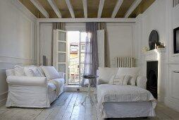 White living room suite with slipcovers in front of an open balcony door and rustic wooden plank floor