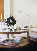 A modern, sitting room, books, glass coffee table, candles, candlesticks, house plant, lamp,