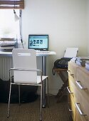 A modern home office with desk, chair, laptop computer, trays, drawers, fax , lamp, radiator,