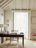 A traditional study room decorated in neutral colours, pattern wallpaper, beamed ceiling, wooden table, chair, lamp, natural flooring, French windows,