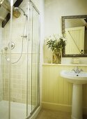Yellow bathroom with shower cubicle and an arrangement of lilies above a washbasin.
