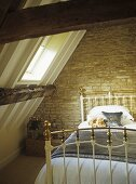 Brass bed with teddy bears under a pitched attic roof and skylight.