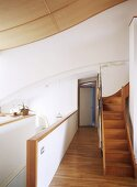 White kitchen area, stairs leading to another room and wooden flooring