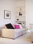 Upholstered sofa with black and pink cushion with shelving in recess