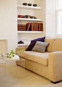 Transparent plastic coffee table in front of upholstered cream sofa