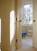 View through partly open doors into cream painted sitting room