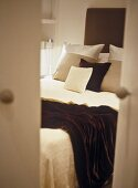 View through partly open doors to double bed with cushions