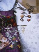 A detail of embroidered fabrics, buttons, scissors,