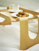 A detail of a wooden breakfast tray on a bed, plate of croissants and white cup and saucer,