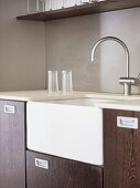 A detail of a modern kitchen, wooden units, a Belfast sink, chrome tap, glasses on draining board,