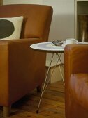 A detail of a modern, brown leather armchair, a round, retro style side table, wood floor