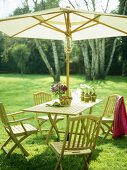 Wooden table and chairs with parasol on lawn.