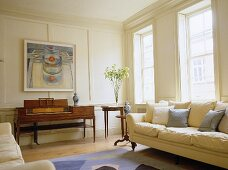 Sitting room with white panelled walls, cream sofa and antique piano.