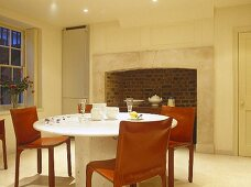 Kitchen round table and retro chairs in front of period fireplace.