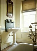 Bathroom with panelled walls and pedestal washbasin with marble spashback.