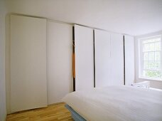 A modern, white minimalist bedroom with double bed, fitted wardrobes, wooden floor, plain window,
