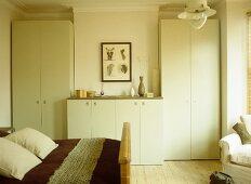 Pair of wardrobes set in recesses in bedroom