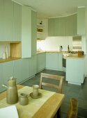 Dining table and chairs in kitchen with green fitted units