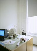 A modern, home office, pair of desks with computers, lamps, half closed blind at the window,
