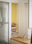 A detail of a modern bedroom, coat hanger stand, shelf recess, books