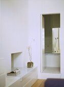 A detail of a modern, white bedroom with view of en suite bathroom,
