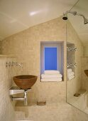 A detail of a modern bathroom in neutral colours, wooden bowl washbasin set on stainless steel shelf, taps, tiled walls, shower unit, folded towels, window,