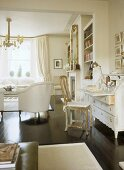 A traditional, white sitting room, polished wood floor, painted bureau, gilt chair, upholstered armchair,