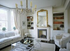 A traditional, neutral sitting room, with fireplace, gilt mirror, book shelves and modern glass coffee table
