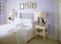 A traditional, pale blue bedroom with double bed, decorative headboard, side tables, lamps