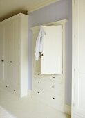 A detail of a pale blue bedroom with painted white, fitted wardrobes, cupboard and drawer unit,
