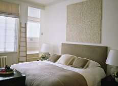 A modern neutral bedroom, double bed with upholstered headboard, side cabinets, textured artwork