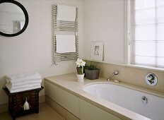 A detail of a modern, neutral en suite bathroom showing bath, chrome towel rail radiator, chest