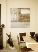 Cream dining room with brown chairs and artwork.
