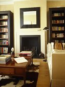 Upholstered sofa facing coffee table in front of fireplace with bookcases either side