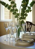 Close up of cream crockery wine glasses and flower arrangement on table