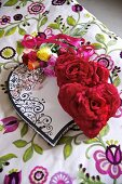 Red heart-shaped cushions with fabric flowers and a bunch of roses on plaid