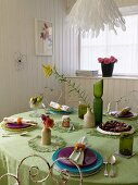 Coloured place settings on a green tablecloth in a white, wood panelled dining room