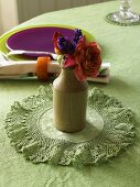 A mini bunch of flowers in a ceramic vase on crocheted mat with a coloured place setting