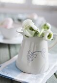 White peonies in a white pitcher with decorative painting on a dish towel