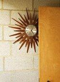 A sun wall clock next to a door