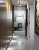 A modern hallway with built-in wooden cupboards and a view through an open door of a chair