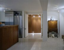 A modern open-plan living room with a kitchen counter and an antique cupboard next to an open door