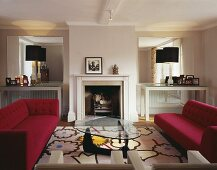 A living room in a period building with a fireplace and furniture in a mixture of styles from Bauhaus to modern